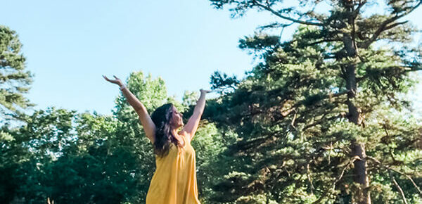 Girl wearing a yellow dress with class Adidas - with hands raised in the air in joy