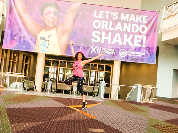 Diana jumping in front of the Let's Make Orlando Shake Zumba Convention banner in front of the Fitness Concert location